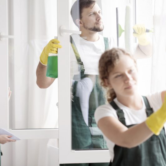 Skilled cleaning team washing windows
